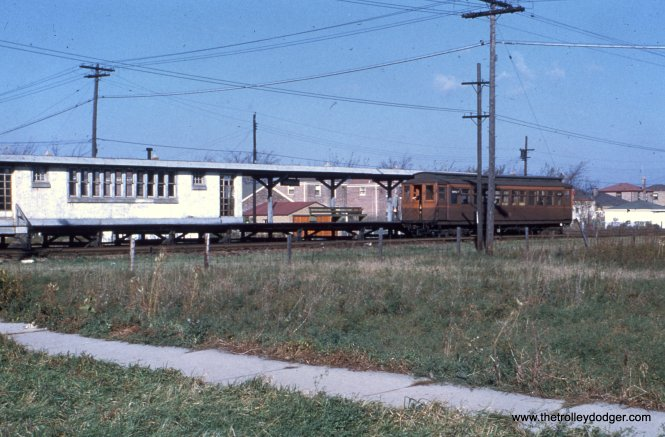 A northbound train at Harrison Street, with new postwar housing in the background. In the foreground, sidewalks that were already about 20 years old go past an empty lot.