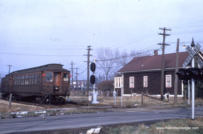 A southbound Westchester train crosses Madison Street in Bellwood, where Marshall Avenue begins today. The house at right is still standing. The Bellwood station was just north of here, near where the line merged back into the CA&E main line. We are just west of Bellwood Avenue.