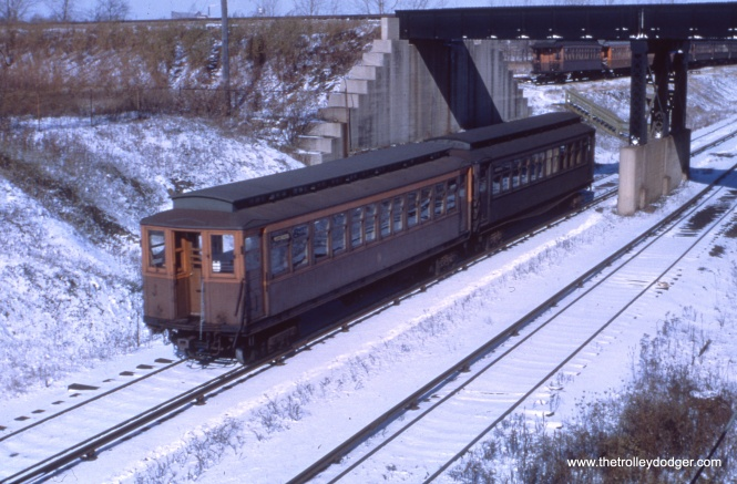 A two car train passes under the Illinois Central near the Roosevelt Road station.