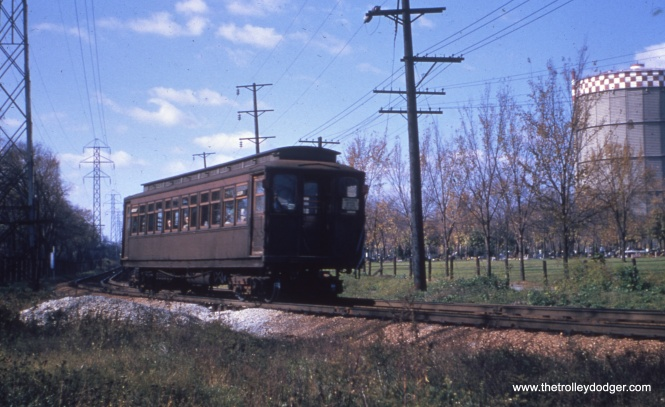 This is one of my favorite shots. An eastbound single car passes cemeteries in Forest Park, having just crossed over the DesPlaines River. This is the approximate location of the Eisenhower expressway today. The train is curving towards the DesPlaines Avenue station. The iconic gas tank was removed many years ago.