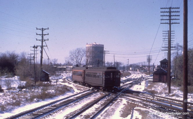 A pair of Met cars crosses the B&OCT heading east. This has since been grade separated. The gas tank in the background was a Forest Park landmark for many years.