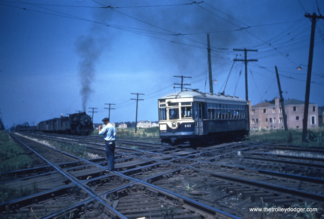 "One of our readers writes, ""the 141 crossing the IHB tracks at Oak Street in LaGrange Park. The car is headed westbound, the train is southbound, possibly entering the sidings that are just south of Oak. The Trolley turned south and paralleled the IHB down to the CB&Q tracks where it turned west along Hillgrove. The home under construction in the background is the second or third house north of Oak on the west side of Beach. """
