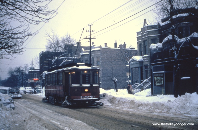 An older streetcar being used as a snow sweeper.