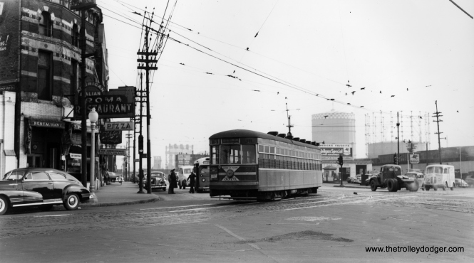 "According to Andre Kristopans, ""The #5 with 3376 is looking SE on South Chicago at Commercial. Note the railroad lift bridges in the distance, past 95th. Also, the bus behind the car is a Chicago & Calumet District bus running on the route that partially replaced the joint CSL/HWEC carlines to Hammond and East Chicago, though the bus route ended up going thru Whiting and then east to Gary, with connections at 119th and Indianapolis for Hammond and East Chicago."" (Joe L. Diaz Collection)"
