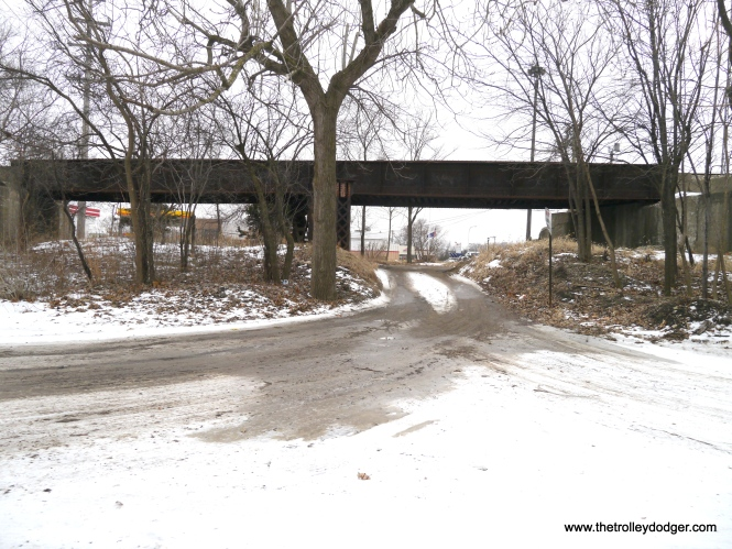 A dirt road passes under the partly filled-in Illinois Central underpass. We are looking south.