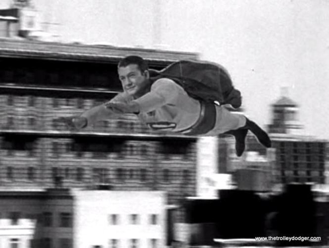 "Due to the limitations of 1950s special effects, here Superman is literally ""flying by wire."" Two wires holding up actor George Reeves are visible against the dark background of Superman's cape."