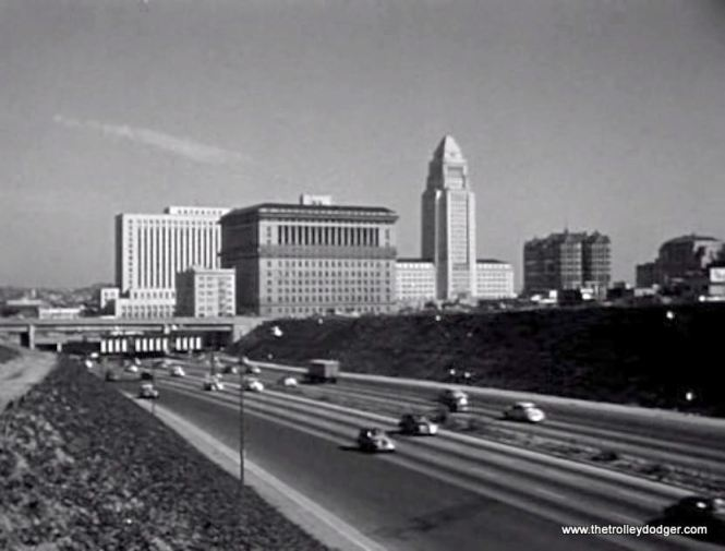 The 1951-57 Adventures of Superman TV series was shot in Hollywood and used the Los Angeles City Hall building at right as the Daily Planet building.  Unfortunately, there's no rapid transit line in the median of this freeway.