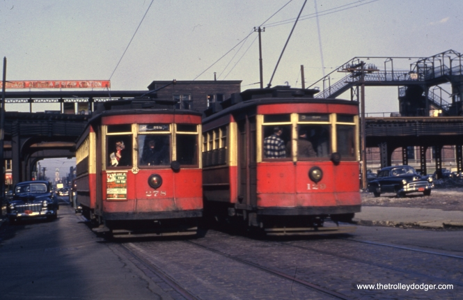 "Red cars 278 and 129 pass at Paulina and Van Buren on route 9 - Ashland. The old Marshfield ""L"" station is at rear."