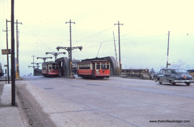 Red cars pass each other on a drawbridge on route 9 - Ashland.  According to Andre Kristopans, this is the Sanitary and Ship Canal at 29th Street or so.
