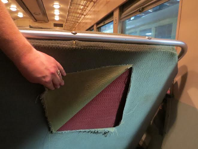 "This one shows a seat that will be reupholstered. You can see the material (cut) that Red Arrow installed; beneath it is the NSL fabric (I believe it was reupholstered once by the NSL.) A swatch of the red material is what will be given to those who ""Buy a Seat"" for $300. (Rod Turner Photo)"