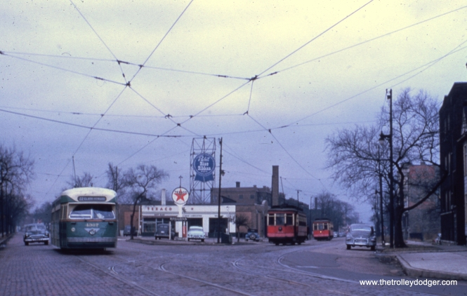 "#45 - Len Marcus says, ""Looking south on Clark Street, at Southport, northbound Green Hornet and end of the line (route 9 Ashland)."" Bill Wasik adds, ""Clark & Southport – View south/southwest. The big Pabst roof neon was on top of a Pabst distributorship that occupied most of this triangular block. Of course, it was only a few blocks north of Wrigley Field, where Pabst had an exclusive with the Cubs for many years. Beer hobbyists may note not only the Pabst display, but also the nearly-unreadable red sign on an apartment building on Southport, visible through tree branches at the far right of the photo. This was a sign for Fox DeLuxe, but not the usual circa 1940 ""Just Taste It!"" signage that still can be seen on several buildings around town, even after 75 years. Instead, the Southport sign was perhaps the last of the Fox painted walls that went up at the dawn of Repeal, when the Peter Fox brewery introduced draft beer in a half-gallon bottle. This ad space on Southport wasn't good, largely hidden from traffic, which may explain why the sign was never painted over. Back in the mid-1960's, it was still visible-enough for me to make it the subject of a 35mm slide, one I wish I still had. In any case, Fox DeLuxe fans even today can search 4117 N. Southport on Google Maps Street View to see what traces of this rare ad remain visible today."" Bill Shapotkin: ""Looking S/B at Clark/Southport. PCC at left is a N/B Clark St car -- at right are Ashland Ave cars in Southport."""