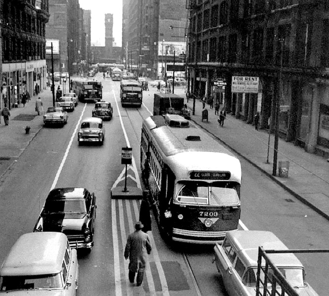 Taken from the Van Buren L stop at Dearborn. Northbound PCC 7203 is at the car stop letting passengers board. Photo was taken in December, 1957 on the last Chicago trolley line. At that time the cars ran only on weekdays. Notice the increasing menace of the Gutterliners (as Ira Swett called them) in the background. © Laurence Mack