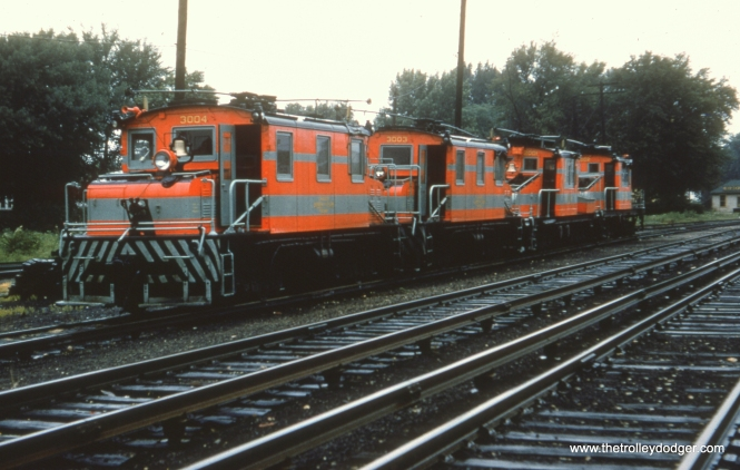 "#13 - WS: Wow! Rare shot of four of the freight locos (the 2000s and 3000s), all in the same paint job. Believe this is on the freight lead (located south of freight yard and west of the two main tracks of Aurora Branch) in front of Wheaton Shop. View looking S/E. EM: North yard of the Wheaton Shops, with 3004, 3003, 2001, and 2002 lined up. AK: Two closest are the ex Oklahoma Ry motors. EM: The two closest locomotives were built by Baldwin-Westinghouse. The two more distant ones were built by GE. The ex-Oklahoma Ry locomotives were numbered 4005 and 4006 and are not in the picture. Bob Campbell: ""Regarding photo #13, in CERA Bulletin #105, page IV-9, the Wheaton map indicates that the four freight motors are sitting on the ""passing siding"" (not the yard lead in the background, at a lower grade level) which is oriented in a NE – SW direction, so the photographer is facing S-S-W, not S-E. In photo #16, the same equipment in the same location as photo #13, the photographer has changed positions and is now facing East, instead of N-E."""