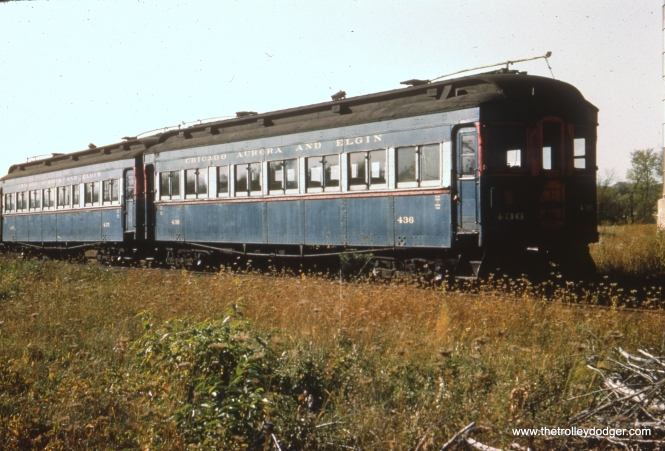 #14 - EM: Two wooden cars that had been parlor cars 600 and 601, rebuilt as coaches with metal added and reconfigured to mate with steel rather that wooden cars, in the north yard of the Wheaton shops at a time when they were seeing little use. WS: These are the two one-time parlor cars — which were built as woods and converted to operate with the steels. Photo taken at Wheaton Yard. Believe view looks N/W. FH: Nice views of the 435-436 prior to scrapping. In the lower photo, I wonder what was cut up ahead of them; I can see a traction motor armature in the pile of metal to the left.
