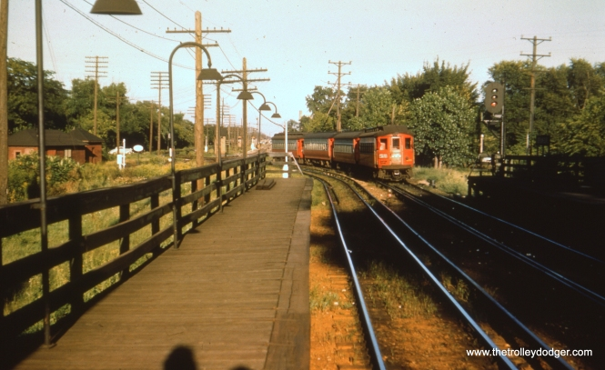 #19 - EM: East end of the old Des Plaines station which was replaced by a fancy interchange on the other (west) side of Desplaines in September of 1953. The shadows, including that of the photographer, indicate this picture was taken in late afternoon, with a four-car steel train with CAE 430 (Cincinnati, 1927) on the end about to cross the tracks of another railroad (B&OCTRR) on its way to downtown Chicago. After the crossing, the two different railroads run parallel almost to Laramie Av. AK: Looking east at Desplaines Av station, B&OCT grade crossing in background, source of many, many delays. (Truman Hefner Photo)