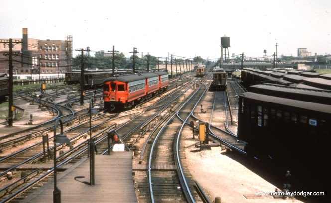 #20 - EM: CAE 458 (St. Louis, 1945) approaching Laramie Av station from the incline leading up to Cicero station, and just visible in the distance, Kilbourn. The view, looking east, includes a vast fleet of wooden CTA cars, with a wooden CTA train about to ascend the incline. The tracks east from here were owned by the CTA. The tracks west of here were owned by the Chicago, Aurora, and Elgin. The tracks west of here to Desplaines Av. were later sold by the CAE to the CTA once CAE trains stopped going east of Desplaines in September of 1953. Notice the monitor style roofs which were distinctive to the Metropolitan line CTA cars. WS: View looks east off footbridge.