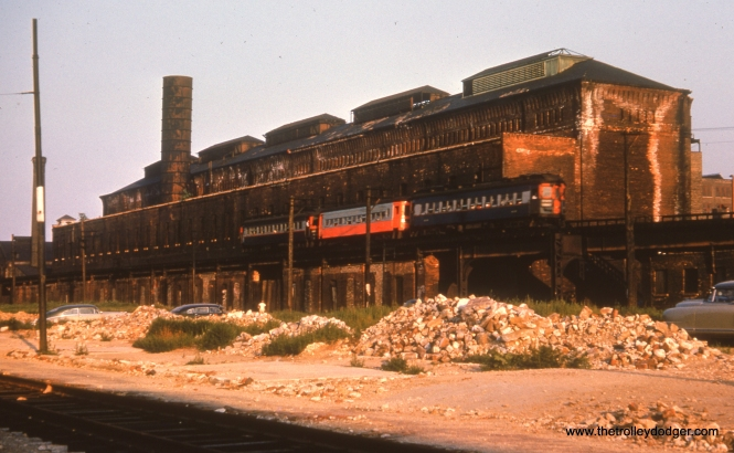 "#27 - WS: An E/B train of steel cars pass the old Met powerhouse. Surrounding buildings have all been demolished in advance of expressway construction. View looks N/W. AK: Throop shop in its last days. Note how bricks are ""leaching""."