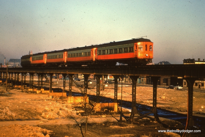 "#38 - FH: Great photo of the 302 leading what appears to be a solid rake of 200/300-series Niles cars (there may be a Hicks in there somewhere, tough to tell from the sides) into the sun. The motorman has his shade pulled down pretty far! EM: CAE 302 (Niles, 1906) leads a four-car train through the wilderness destined to become the Congress Expressway. Van Buren Street, future site of the infamous ""stop light express,"" can be seen. AK: approaching CNW/PRR at Rockwell WB. Photo from PRR tracks note brick structure bases, then last few are steel. Structure was raised when PRR/CNW was elevated. Richard Neva adds, ""Number 38 appears to show Our Lady of Sorrows Church with 2 spires in the background which I was very familiar with during my early growing years."""