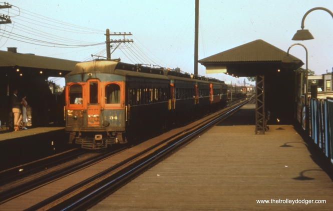 "#40 - FH: Nice shot of a five-car rush-hour train of ""shorties"" at Kedzie, express to Wheaton if the sign is to be believed. The 34 is still in tattered blue and retains its light grey roof, or what's left of the paint anyway; a lot of cars had their roofs tarred in the late 1940s/early 1950s. It looks like the motorman has drawn the curtain over the ""railfan window"" in the bulkhead so that the commuters don't all have the sun in their faces. And it's tough to tell but it looks like an ex-North Shore wood car in the background on the curve."