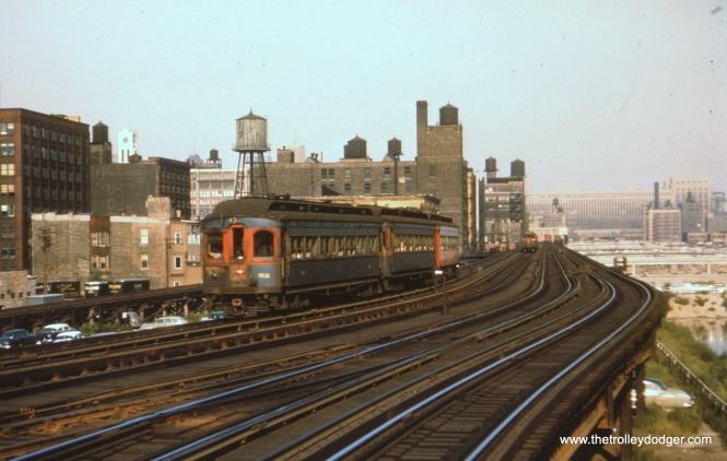 "#41 - WS: W/B train of woodies approaching Racine Ave. Note the ramp (at left) leading down to Van Buren St trackage — places the time frame as 1953 (no earlier than June or July?). View looks east. FH: A slightly unusual consist, as the ""shorties"" were often segregated and run together. But here we have two ""shorties"" followed by what I believe is a Jewett westbound at Racine on a local. EM: CAE 52 (Stephenson, 1902) leads a three-car westbound train between Racine and Halsted. I suspect that the track at far left is under construction for the east end of the infamous ""stop light express,"" to allow the destruction of the tracks in the foreground for the construction of the Congress Express, which can be seen at the right. Looking east. These tracks will soon be far less used because of the loss of the CAE, and all CTA trains except the Garfield Pk. AK: Looking east from Racine, track in center is Throop shop lead."