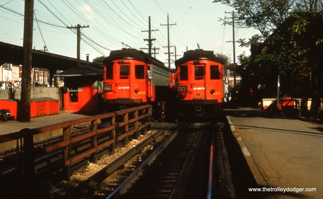 #44 - EM: CAE 422 and 434 (both Cincinnati, 1927) at Wheaton station. Notice all the fresh red paint. Also notice the jumper cables hanging from the not recently painted fence. WS: Two trains meet at Wheaton station (note C&NW station at left). View looks east.