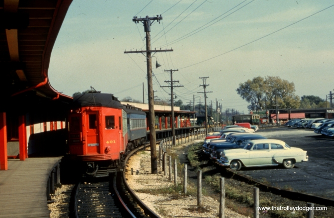 "#94 - JN: Train on outbound platform at Desplaines Ave. Note ""baldy"" heading to Chicago in background. EM: CAE 401 (Pullman, 1923) leads a two car consist at the new (1953–1957) station on the west side of Des Plaines Av. At this time the CAE trains turned around without crossing Des Plaines Av. The CTA trains discharged all passengers at this station. Those who want to go further west boarded a CAE train here and paid another fare. The green and cream train in the background has just come from their station (color-coded green) on the other side of the loop where the CAE trains discharged all their passengers. Those wishing to continue east had to pay another fare to the CTA. the loops did not cross at grade, there was a wooden structure to carry the CTA trains above the tracks of the CAE. All the tracks east of Des Plaines Av, formerly owned by the CAE as far as Laramie Av, were sold to the CTA."