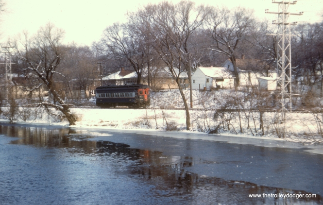 #60 - JN: Eastbound under short stretch of trolley wire on Batavia branch. EM: A single car travels along the Fox River in the snow.
