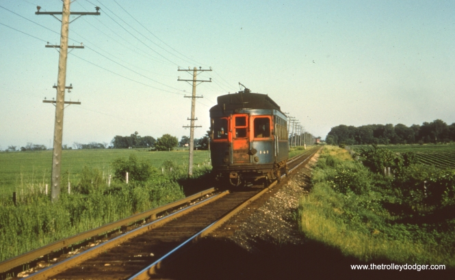 "#62 - JN: Batavia bound car having departed from Batavia Jct. (in distance). EM: CAE 141, a car obtained second hand from the North Shore Line travels through the middle of nowhere, I would guess on the Batavia branch. Bob Campbell says, ""141 is on the Aurora branch; not Batavia branch. West of Batavia Jct. was tangent on the Aurora branch. Batavia line just west of BJ was on a curve (see photo #66)."" Bill Shapotkin writes, ""While not disputing that this photo is taken on the Batavia Branch, the remark: ""car having departed from Batavia Jct. (in distance)"" I believe is incorrect. The reason I say that is that upon departing Batavia Jct (enroute to Batavia), the line IMMEDIATELY goes through a long sweeping curve to the N/W (as can be see in Photo 58). While I do not know exactly where this photo was taken, be assured that the distant station in photo is NOT Batavia Jct. By the way, this is NOT ""pull-in"" trip of the Batavia car (enroute to Wheaton after the PM rush). If it were, the platform of Batavia Jct would be to the right (not to the left). I believe the photo is at either one of two locations: 1. A point JUST north of Bilter Rd (as the State Rd station would be on west side of R-O-W), or 2. A point JUST N/W of the sweeping curve out of Batavia Jct -- approx where East-West Tollway intersects the line today (thus station in distance is Bilter Rd (which, like State Rd was located on west side of R-O-W). In either case, believe this is a morning photo (of an E/B car) and that we are facing geographically N/W."""