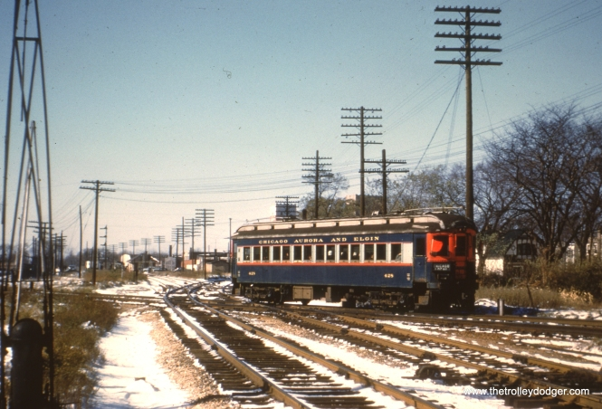 #77 - JN: Westbound train crossing B&OCT east of Desplaines Ave. station. EM: CAE 428 (Cincinnati, 1927) crosses the B&OCTRR just east of Des Plaines Av. The branch going west along side the CAE tracks in the distance were for the Chicago and Great Western. Notice the old style crossing gate at left in the foreground. View is looking mostly west and slightly NW.