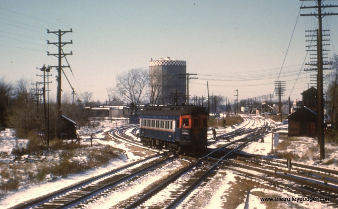 #79 - JN: Eastbound train has left Desplaines Ave. station and crossing B&OCT EM: CAE 428 (Pullman, 1923) at the same B&OCTRR crossing as in picture #77, but this time it is headed east. View is looking west.