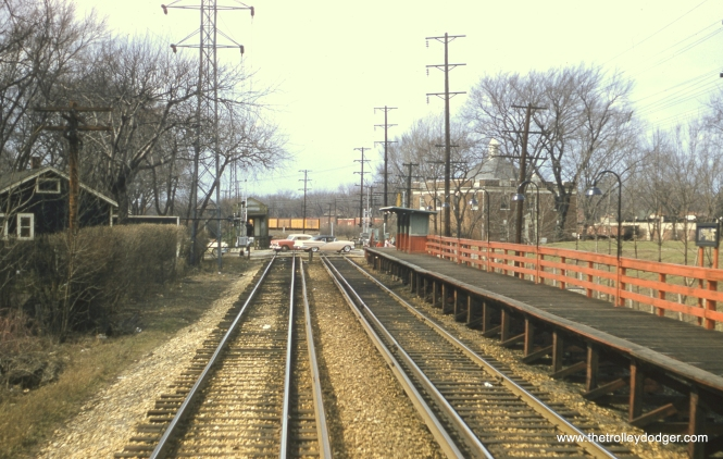 "#86 - JN: View west of 11th Ave. in Maywood EM: Station at 11th Av. in Maywood. The red railings show that this is a late picture, since they were painted green when the CTA trains of the Westchester branch stopped here for the last time December 8, 1951. Notice the newer automobiles crossing 11th Av. Dan Cluley adds, ""the cream colored convertible is a 1957 Olds. So given the bare trees this must have been taken in the Winter or early Spring of '57."""