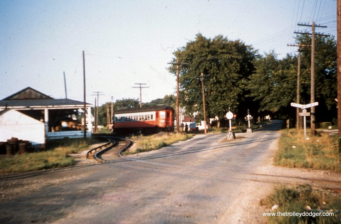 "#88 - JN: Westbound train on Aurora branch at Childs St., Wheaton EM: Now this is truly a ""mystery"" photo! The street crossing looks like something out of the 1920's, but the Pullman car is painted in the last livery! Someone else will have to explain this one! Bob Campbell writes, ""Agree Childs Street, Wheaton looking east."""