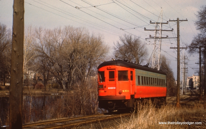 #91 - JN: Eastbound train departing Batavia terminal at Wilson St. EM: CAE 460 (St. Louis, 1945) still is running under wire along the Fox River. It has just left the Batavia station, headed for Chicago. View is looking NW.
