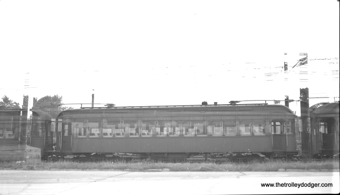 "#11 - Although this is a double exposure, it does show an unnumbered wooden interurban, ex-Chicago, North Shore & Milwaukee in Wheaton in 1946. It was part of the 129-144 series, the last passenger cars purchased by CA&E. Don's Rail Photos says, ""In 1936, the CA&E leased 11 surplus cars from the CNS&M. These cars were modified for service by raising the coupler height, installing electric heat instead of the coal-fired hot water heaters, modifying the control, and adding jumper receptacles and other minor fittings to allow them to train with the other CA&E cars. Since these were 50 mile per hour cars, and the CA&E cars wer 60 MPH cars, they were soon operated only in trains of their own kind rather than mixed in with other cars. In 1945 they were returned to the North Shore where they operated briefly. They were purchased in 1946 and last ran in regular service in September, 1953."""
