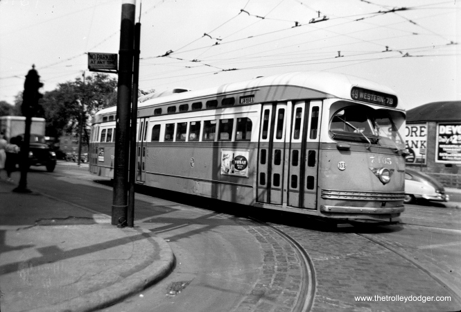 "Jeff Wien writes, ""PCC 7165 is a route 49 Western pullout from Devon Station (Clark and Schreiber). Car is pulling off of Clark onto Devon to head west and south along Western to 79th St. In back of photo one can see the wall of the Ridge Theater that later became a part of the Clark-Devon Hardware Store."""