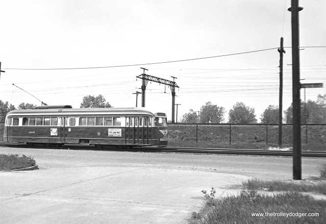 "CTA 4049 on that section of Cottage Grove that ran parallel to the Illinois Central electric suburban service (now Metra). The ad of the side of the PCC, advertising the Mickey Spillane film ""The Long Wait,"" currently playing at the Woods Theater, dates this photo to between about May 19 and June 14, 1954."