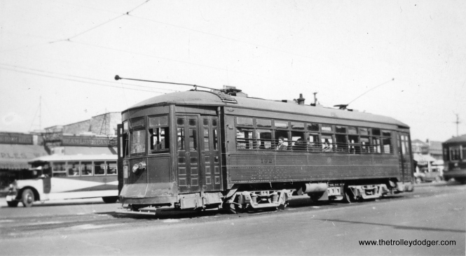 "Chicago & West Towns 102 is shown at Cermak and Kenton in October 1935, with a Chicago Surface Lines route 21 car at rear. Within a few years, C&WT streetcars were repainted into the more familiar blue. Bill Shapotkin adds, ""By the way, what bus is that depicted at left in this photo at Cermak/Kenton? Presume it is a West Towns bus (in the ""sun burst"" paint job) -- but if so, what route is it working? If not a West Towns' bus, then whose might it be and what route is it working?"""