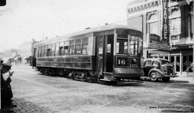 "Another view of a Lake Street car at the west end of the line, at Lake and Austin, in September 1939. Car 1579 is parked in front of the Park Theatre, this time showing a double feature of Four's a Crowd and Stronger Than Desire. Meanwhile, it looks the the motorman and conductor are taking a break at curbside. The Park is still advertising that it shows ""Talkies,"" which became popular in 1927, and the sign that says ""Refrigeration"" means that the theatre was already air-conditioned. The streetcar is working through-route 16 and is signed for State-79th."