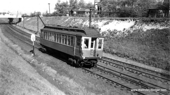 A single car Niles Center train in the open cut in Evanston.