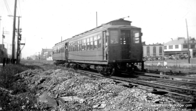 "A two car CRT ""L"" train in December 1935. The location is given as Austin, but the photo does not indicate whether this is the Douglas Park branch or Garfield. Bill Shapotkin writes: ""I can't tell you where this pic was actually taken, but I can tell you where is was NOT taken. This photo is NOT on Garfield Pk/Westchester. If it were anywhere on that line, the third rail chairs would be the CA&E's wooden third rail chairs -- the chairs shown in this photo are rapid transit third rail chairs. Additionally, if it were ""Austin"" (on Garfield Pk), we should see the B&OCT next door (and it is not). Now, as for where I think this photo was taken -- there appears to be an interlocking nearby (notice the piping next to outside rail). Thus, I believe the train is WB on DOUGLAS approaching Oak Park Ave (where, if I recall correctly) there was an interlocking. Therefore we would be looking east. At least that is my best guess."""