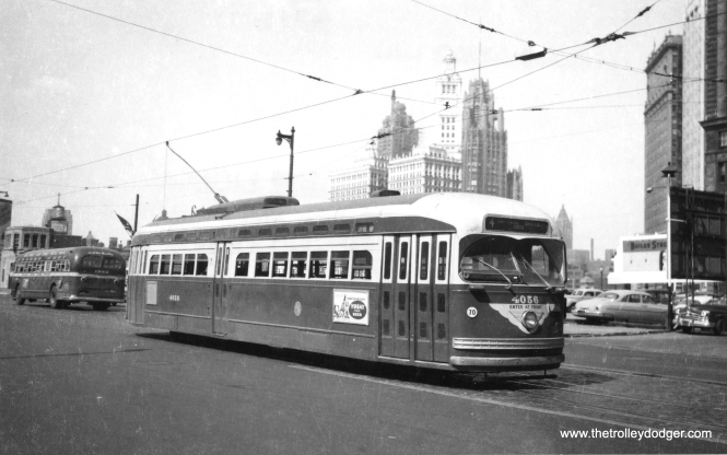 St. Louis-built PCC 4056, signed for route 4 - Cottage Grove, has just crossed the Chicago River. While the iconic Wrigley Building and Tribune Tower are at rear, the Sun-Times building (1958) had not yet been built when this picture was taken. Note a Chicago Motor Coach bus at rear. CTA purchased Motor Coach's assets as of October 1, 1952, probably not too long after this picture was taken. In the 1950s, some Cottage Grove cars (usually signed as Route 38) went north of the river and terminated at Grand and Navy Pier. (Railway Negative Exchange Photo)