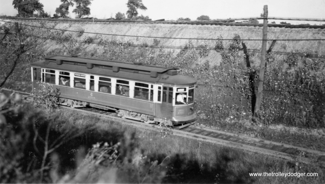 "Bill Shapotkin writes: ""This pic is on the Riverdale line. The location is JUST SOUTH of 130th St (the tracks on the embankment are the IC). View looks E-N/E."" George Trapp: ""CSL #2595 is on Riverdale line, side sign reads Michigan-Indiana."" M. E. writes: ""The first picture is on the Riverdale line, which ran south along the west side of the Illinois Central main line, then under the IC, then south to Riverdale."" The car number looks like 2595, making this a ""Robertson"" car, built by St. Louis Car Company in 1901. Robert Leffingwell writes: ""(This) picture is most likely Indiana Ave between 130th and 134th where it ran on private right of way along side the IC tracks. (The tracks on 134th are still clearly visible to this day)."" Andre Kristopans: ""2595 is on 34-Riverdale (sign would say Michigan-Indiana) along the IC between 127th and 134th."""