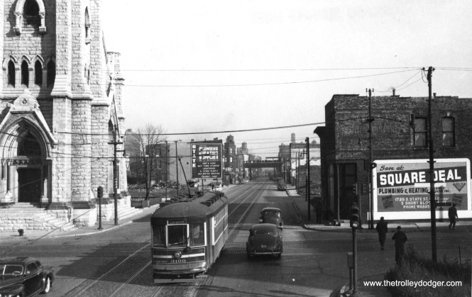 "CSL 3100. If the sign at right is any indication, that is probably the South Side Park ""L"" at rear. (Railway Negative Exchange Photo) M. E. thinks this streetcar is on the 18th Street line, which ""started at Leavitt (2200 West) and Blue Island, went north on Leavitt to 18th St., then east to probably Michigan Ave."" George Foelschow: ""I believe 3100 is eastbound on 18th Street crossing South Clark Street. There was a Catholic church at 18th and Clark. The 18th St. line ended at State. Track on 18th east of State and Wabash turned south on Indiana and was used by Indiana and Cottage Grove cars."""