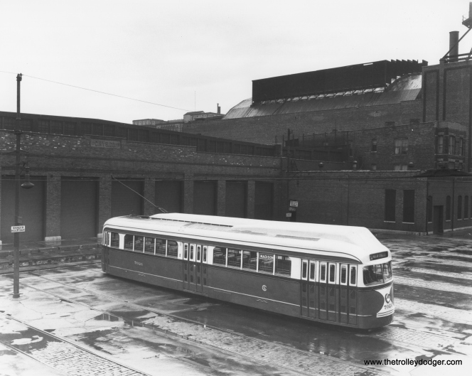"PCC 7026 at West Shops, temporarily fitted with experimental roof-mounted forced air ventilation, of a type that was used in Boston, but did not find favor in Chicago. (CSL Photo) Chuck Amstein adds, ""The large building behind the shop building is the back of the Paradise Theatre, 231 N. Crawford/Pulaski. It was one of the last big movie palaces built in Chicago (1928) and one of the first to be torn down (1956)."""