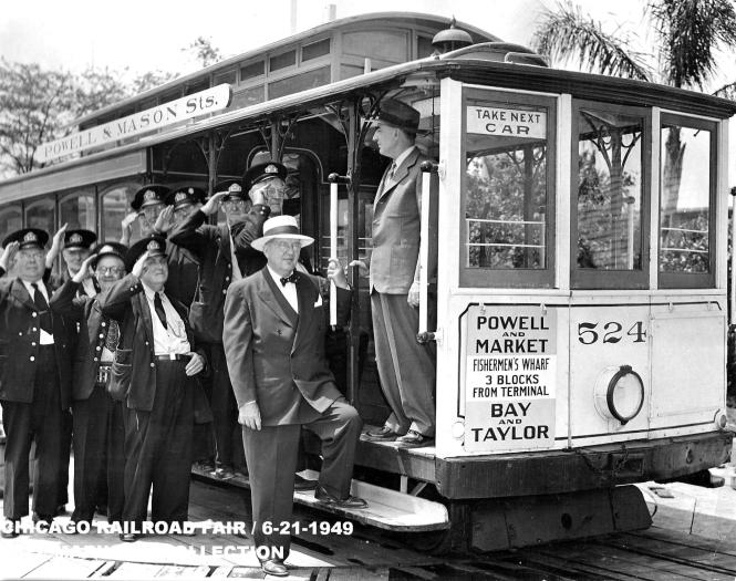 "San Francisco cable car 524 at the Chicago Railroad Fair on June 21, 1949. (Jeff Marinoff Collection) One of our readers notes, ""Most of the gentlemen shown in transit uniforms appear to be wearing caps that have the Chicago Surface Lines cap badge on them in spite of the fact that according to the date on the photo the CTA had been in existence for almost two years. The guy with the coin changer might be wearing a CTA cap badge of the period."" Interesting. Guess things didn't get replaced immediately. ""They were also slow to slap the CTA decals on some of the streetcars too."""