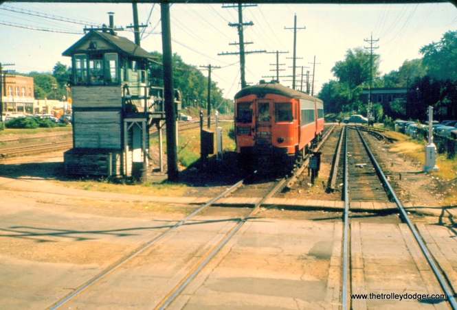 "This 1955 photo's a bit of a mystery. Could this be Wheaton? William Barber: ""Yes, this is Wheaton at the grade crossing immediately east of the depot."" The location is Main Street looking east."