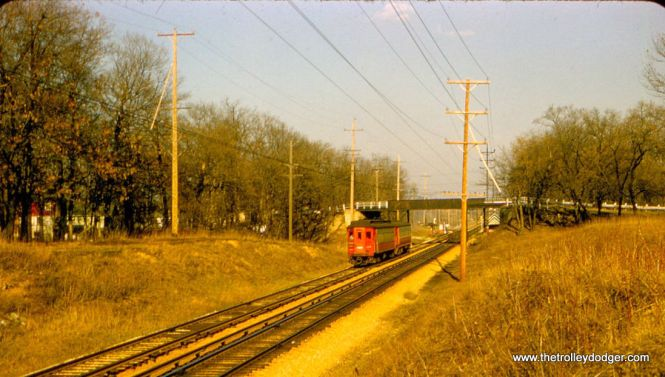 "CA&E 406, in this 1957 picture, is identified as being at Fifth Avenue in Maywood. Perhaps one of our keen-eyed readers can confirm this. This is either late afternoon or early morning light, which explains why the sky is blue but most everything in the picture is yellow. That's one reason why the CA&E was known as the ""Sunset Lines."" Bill Shapotkin: ""This pic NOT anywhere near Maywood. It is WEST of Hill Ave (aka Glen Oak Rd) in Glen Ellyn. Beyond the bridge is the Glen Oak station. View looks east."""