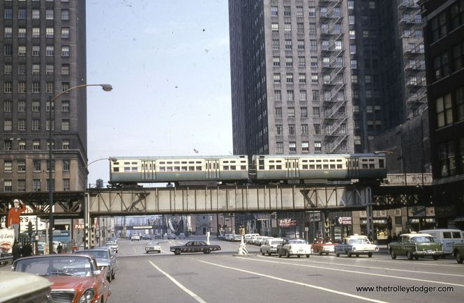 "A two-car train of CTA 6000s heads west at Lake and LaSalle in April 1964. Below the ""L"" at right, we see the Loop location of Discount Records, a local chain who once had a great selection of LPs."