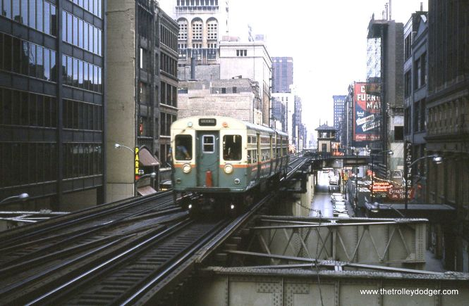 "In July 1963, a two-car CTA Ravenswood train of 6000s approaches Adams and Wabash from the south. When this picture was taken, both tracks on the Loop ""L"" ran in the same direction. At right we can see Carl Fischer's, sellers of sheet music for many years, at 312 S. Wabash."