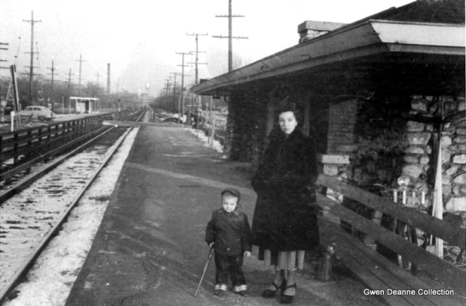 "Gwen Deanne writes: ""My mother wearing the most fabulous shoes ever, and my brother exercising his ""open carry"" rights as a youngster bringing a BB gun on the train. This is 100% Chicago, but which station, I don't now. Perhaps you can figure it out. They lived on North Talman at the time, but Nana lived in Wicker Park. They could have been going anywhere. Taken by my Dad. The next brother was born, and not pictured. He may be with Nana, or Auntie Olga."" Mike Murray: "" That's the Ardmore station of the Chicago, Aurora, & Elgin Railroad, facing east in Villa Park. The station is still there, but the railroad quit passenger service on July 3, 1957. Much of the route is now the Prairie Path. The silver water tower in the distance is the Ovaltine Factory."" Here is another picture of the same station: http://www.greatthirdrail.org/stations/main/ardmore.html (Photo from the Gwen Deanne Collection, used by permission)"